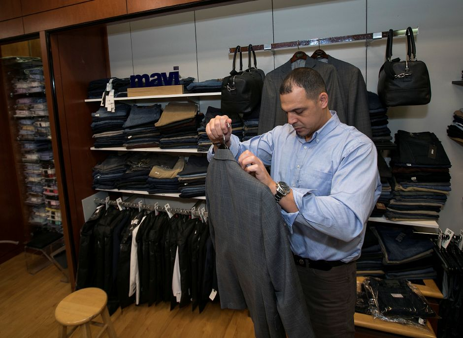 Sam Grain, salesperson, readies a suit for the rack at Ramani