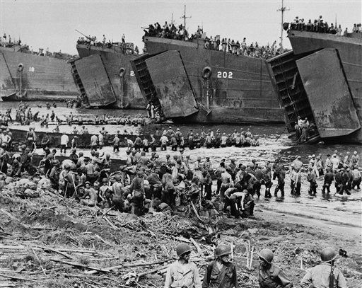 Passing sandbags hand-to-hand, American troops build ramps to the open bow doors of a line of coast guard manned LSTís at the beach of Leyte Island in the central Philippines on Nov. 14, 1944, as supplies are brought in to support invading forces. (AP Photo)