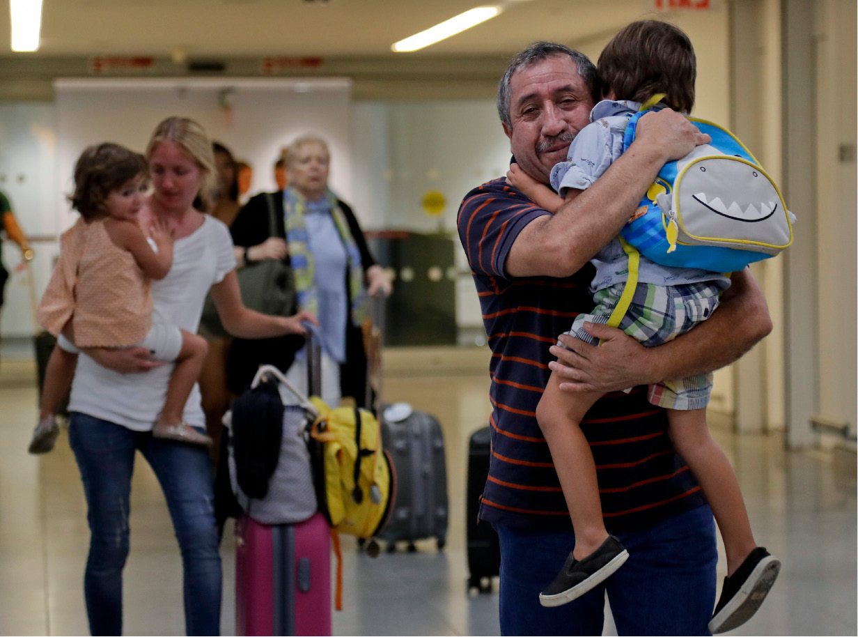 Juan Rojas, right, of Queens, hugs his 4-year-old grandson Elias Rojas, as his daughter-in-law Cori Rojas, left, carries her daughter Lilly, 3, through the terminal at JFK airport after Cori arrived on a flight from San Juan, Puerto Rico, Tuesday, Sept. 26, 2017, in New York. Cori Rojas, who is a school teacher in Puerto Rico, fled Puerto Rico with her children after Hurricane Maria left the island devastated and will stay with her in-laws in Queens while her husband, who works for a global insurance firm chose to stay behind. (AP Photo/Julie Jacobson)