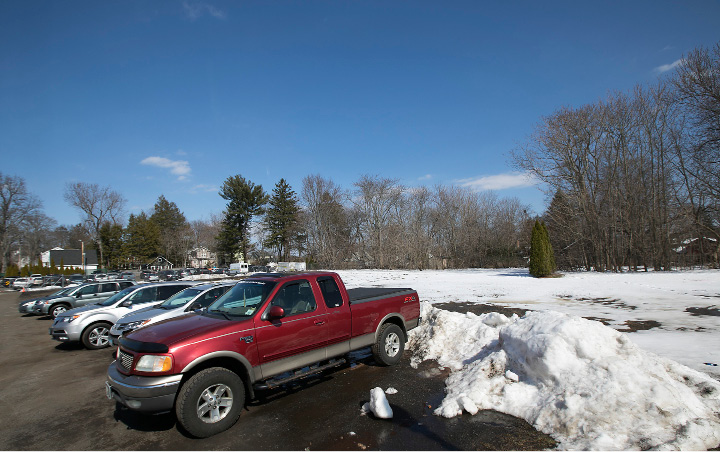 Vehicles parked near the end of Wallace Avenue in Wallingford on Tuesday. The field behind the vehicles has been proposed for additional parking.  | Dave Zajac, Record-Journal