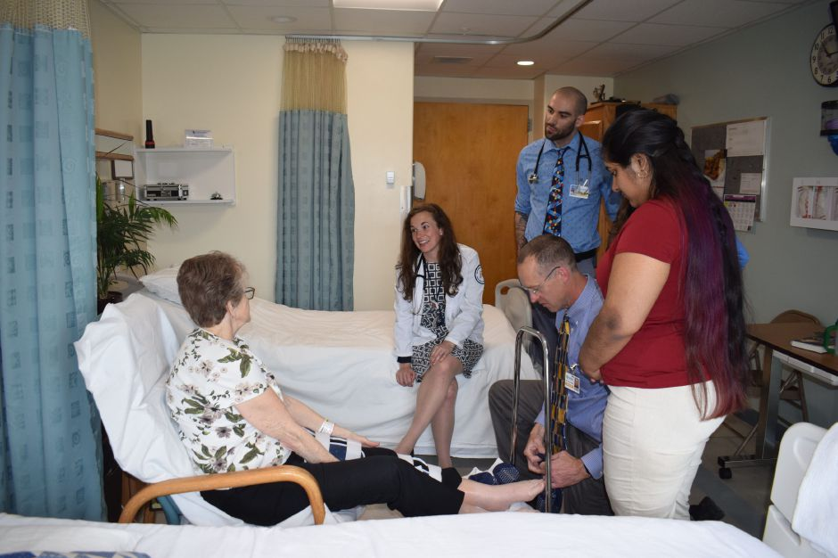 Dr. Michael Sullivan attends to a patient while residents Zoe Frolking (seated), David Piscitelli and Jessica Malhotra watch. Photo courtesy of Quinnipiac University.