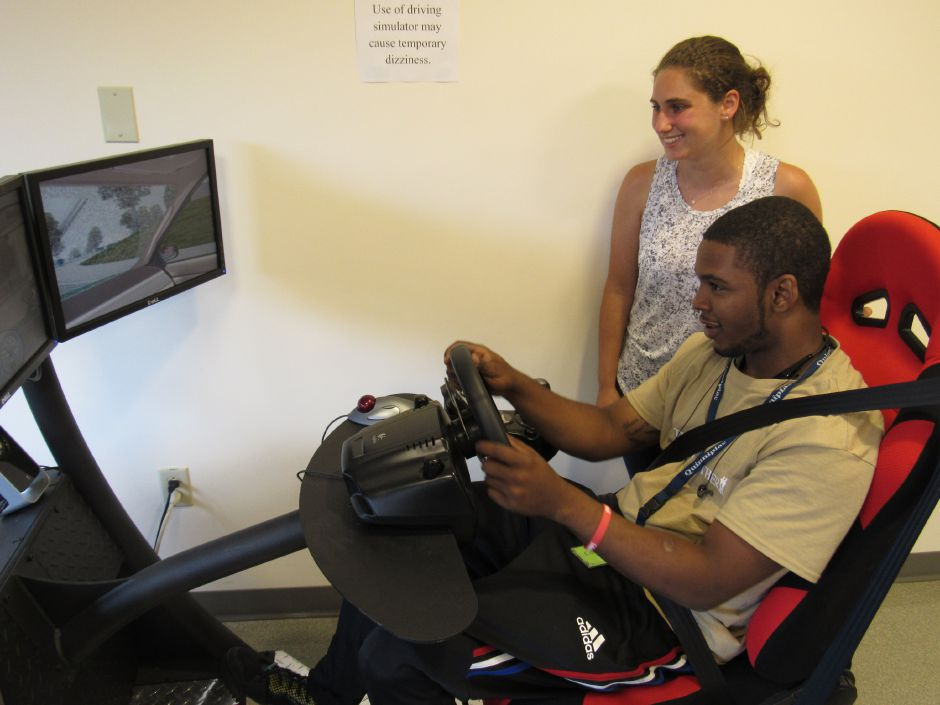 CorRales Dupree, of Richmond, Virginia, tests out a driving simulator  during a teen program at Camp No Limits on Quinnipiac University's North Haven campus as Quinnipiac grad student Melissa Frank observes on Wednesday, July 11, 2018.  | Lauren Takores, Record-Journal
