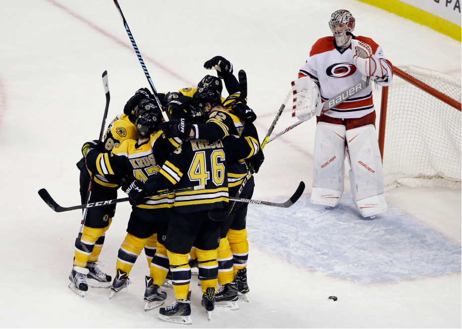 Carolina Hurricanes goalie Cam Ward (30) watches as Boston Bruins players celebrate a goal by defenseman Torey Krug (47) to tie the game with seconds to go in the third period of an NHL hockey game, Thursday, Dec. 1, 2016, in Boston. The Bruins won, 2-1, in a shootout. (AP Photo/Elise Amendola)