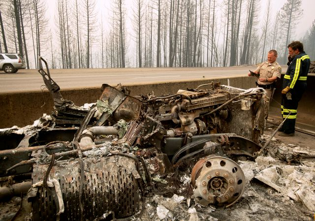 California Capt. Mark Loveless examines a scorched license plate on Interstate 5 as the Delta Fire burns in the Shasta-Trinity National Forest, Calif., on Thursday, Sept. 6, 2018. The highway remains closed to traffic in both directions as crews battle the blaze. (AP Photo/Noah Berger)