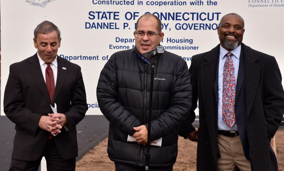 Housing and Community Development Manager with the Department of Housing, Miguel Rivera (center), with First Selectman Michael Freda (left) and Dominic Carew, Housing Specialist with DOH, during a dedication ceremony at Parkside Manor, 191 Pool Rd. The town recently completed exterior site improvements and replacement of the fire alarm system thanks to a grant from the U.S. Department of Housing and Urban Devleopment through the Small Cities Program. | Bailey Wright, Record-Journal