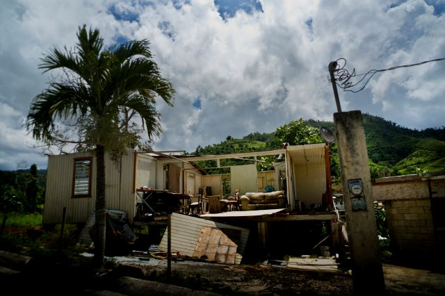 In this Sept. 8, 2018 photo, a home that was abandoned after Hurricane Maria hit one year ago stands full of furniture in the San Lorenzo neighborhood of Morovis, Puerto Rico. Puerto Ricans living below the poverty line were pushed to the brink of despair by the storm, struggling for food, housing and medicine. (AP Photo/Ramon Espinosa)