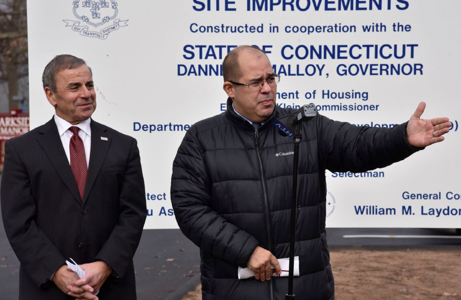 Housing and Community Development Manager with the Department of Housing, Miguel Rivera (center), recognizes fellow collaborators during a dedication ceremony at Parkside Manor, 191 Pool Rd. The town recently completed exterior site improvements and replacement of the fire alarm system thanks to a grant from the U.S. Department of Housing and Urban Devleopment through the Small Cities Program. | Bailey Wright, Record-Journal