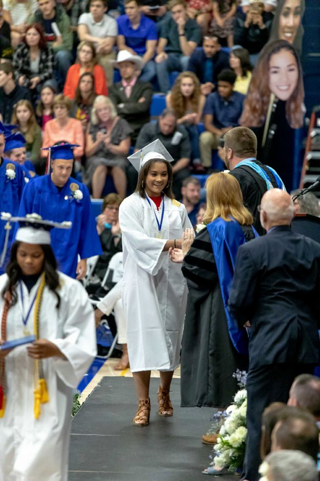 A student walks across the stage to receive their diploma during the Plainville High School graduation ceremony, held in the school