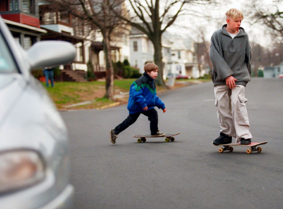 RJ file photo - Bobby Benigni, pushes off to gain speed to keep up with his older brother Henry Owen, as they skateboard after school across Griswold Street in Meriden, Dec. 1998.