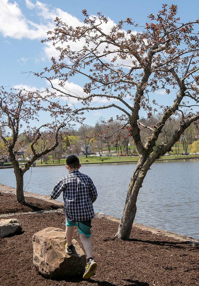 Avi Chernin, 11, of Waterbury, jumps on boulders along Mirror Lake at Hubbard Park in Meriden, Tues., Apr. 23, 2019. Dave Zajac, Record-Journal