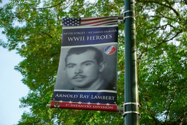 A banner honoring D-Day survivor Ray Lambert hangs on a post near the entrance to the American Military Cemetery in Colleville-sur-Mer, France, on Wednesday, June 5, 2019. Lambert was a Army medic with the 16th Infantry Regiment and was wounded four times in the June 6, 1944, invasion