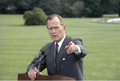 U.S. President George H. Bush stops to talk with reporters on his way to Camp David, Md., for the weekend, Friday, Sept. 21, 1990 in Washington. Bush commented on the Middle East turmoil and the budget process. (AP Photo/Charles Tasnadi)