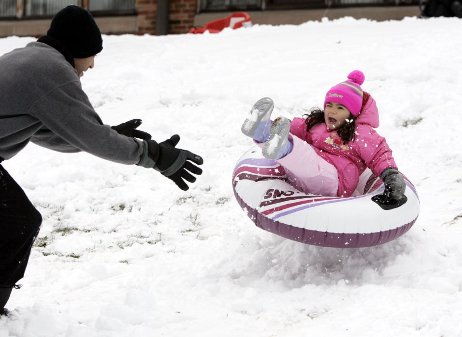 Joby [cq] Rogers is ready to catch his daughter, Aubree [cq] Rogers, 3, as she flies off a little snow ramp sledding behind Nathan Hale School in Meriden, Monday, Jan. 14, 2008. With school canceled, many kids went out to play in the snow.