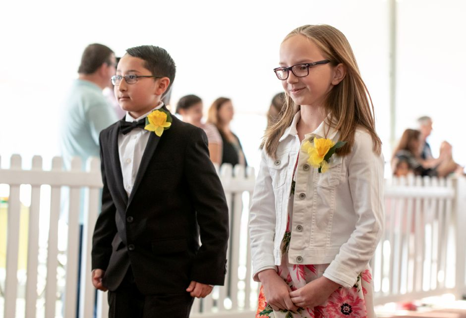Emma London, 9, right, and Jorden Parrilla, 9, of Thomas Hooker Elementary School, are presented to the crowd at the crowning ceremony of Miss Daffodil on April 24, 2019. The selected elementary schooler and her escort will head the Meriden Daffodil Festival Parade on April 27. | Devin Leith-Yessian/Record-Journal