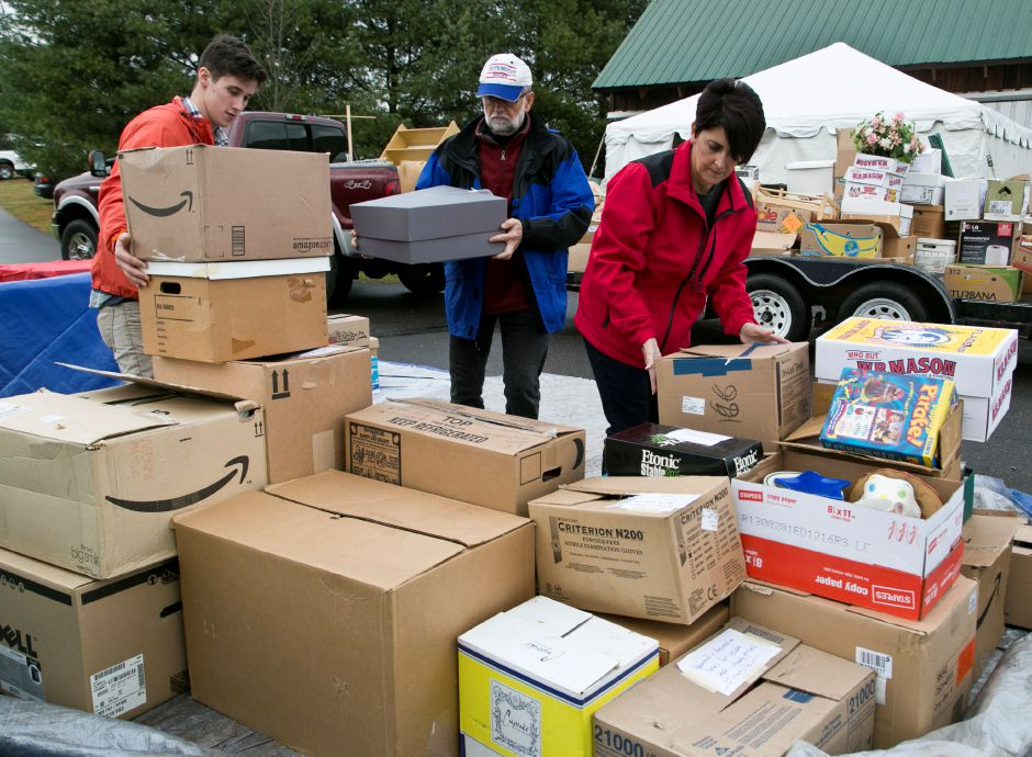 From left, Noah Corey, of Meriden, Paul Grenier, of Southington, and Cindi DeLaurentis, of Wallingford, all volunteers, unload a truck and stack boxes as they prepare the items for the Merry Miscellaneous tag sale section at the annual Franciscan Christmas Fair on Nov. 22, 2013. The fair will be on Saturday, Nov. 23 from 9:30 am to 2:30 pm. | Christopher Zajac / Record-Journal