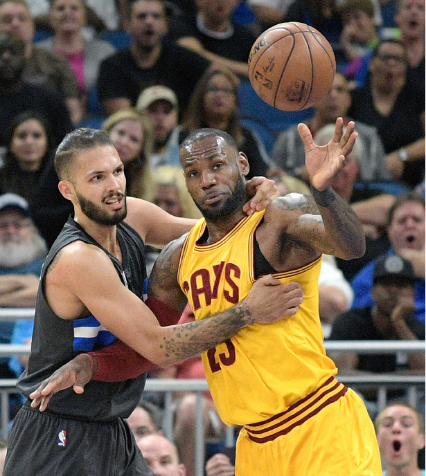 Orlando Magic guard Evan Fournier, left, and Cleveland Cavaliers forward LeBron James (23) fight for a rebound during the first half of an NBA basketball game in Orlando, Fla., Saturday, March 11, 2017. (AP Photo/Phelan M. Ebenhack)