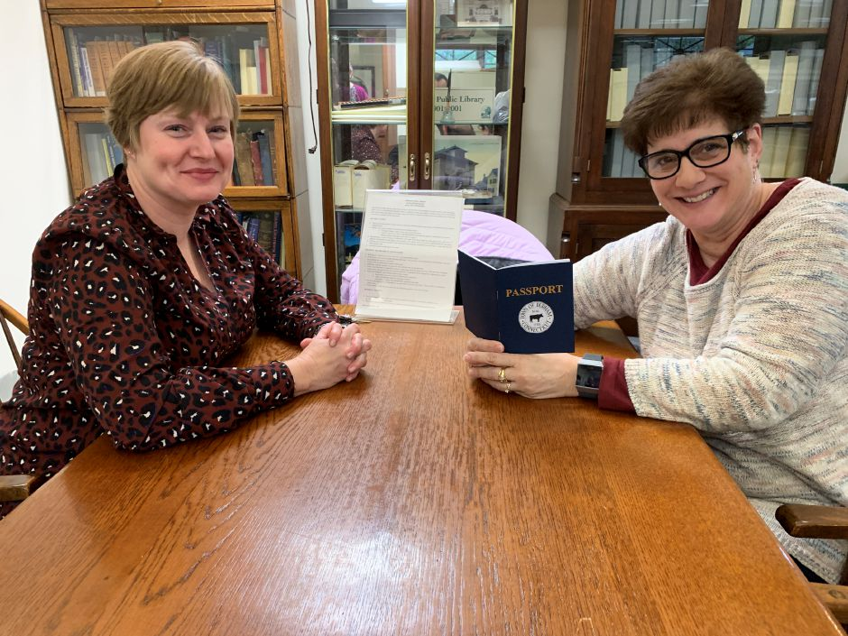 Assitant Library Director Kim McNally (left) sits beside Durham EDC Chair Janet Morganti (right) as they take a look at the Small Business Saturday passports. Photo by Everett Bishop, Town Times.