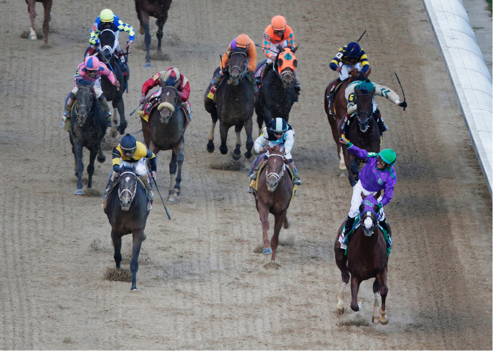 Victor Espinoza, lower right, celebrates as he rides California Chrome to victory during the 140th running of the Kentucky Derby horse race at Churchill Downs Saturday, May 3, 2014, in Louisville, Ky. (AP Photo/Charlie Riedel)