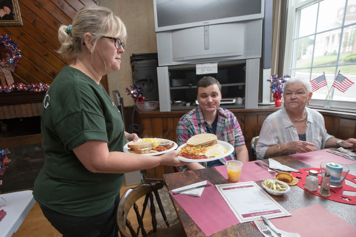 Carol Sadlowski left serves orders to Michael Botsacus and Cher Collins Sunday during the inaugural Father
