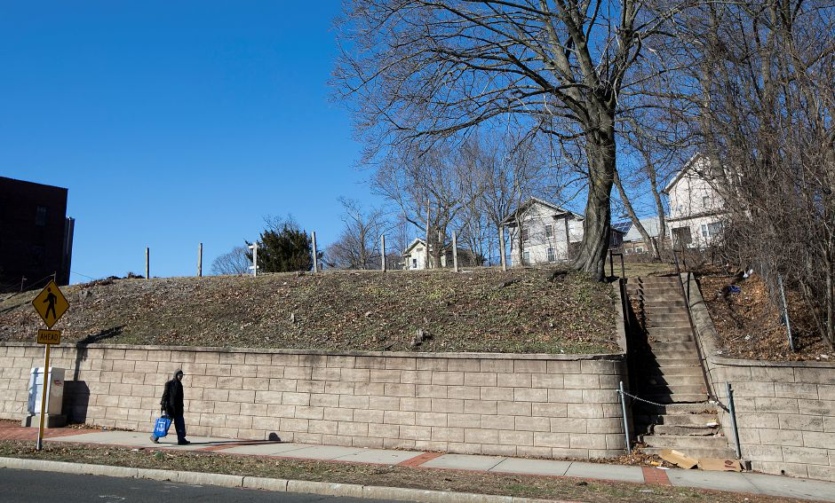 A man walks by a vacant lot at 143 W. Main St. in downtown Meriden, Tuesday, February 27, 2018. The Meriden Housing Authority has selected a development partner to build 45 market rate apartments on the corner of Maple Branch and Maple Street. Houses on Maple Branch are seen in the background behind the lot. Dave Zajac, Record-Journal