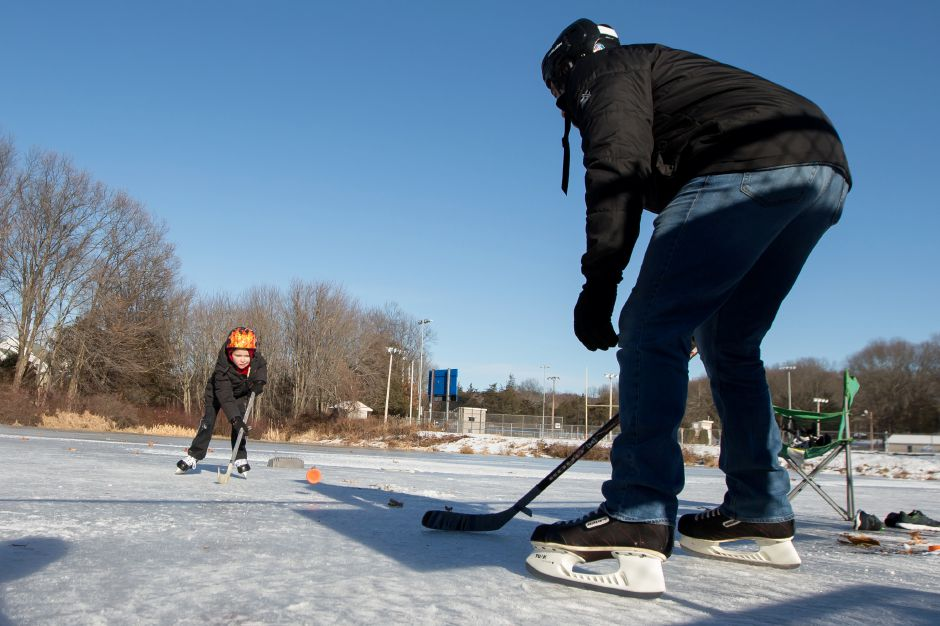 Connor Santiago 7 of Southington plays one on one hockey with his father Dan Santiago Friday at Memorial Park in Southington December 29, 2017 | Justin Weekes / Special to the Record-Journal