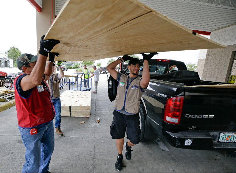 Employees of a building supply store load sheets of plywood for a customer in the back of a truck during preparation for Hurricane Irma, Wednesday, Sept. 6, 2017, in Orlando, Fla. Throughout Florida, officials and residents are making preparations, but forecasts indicate the Keys could take the country