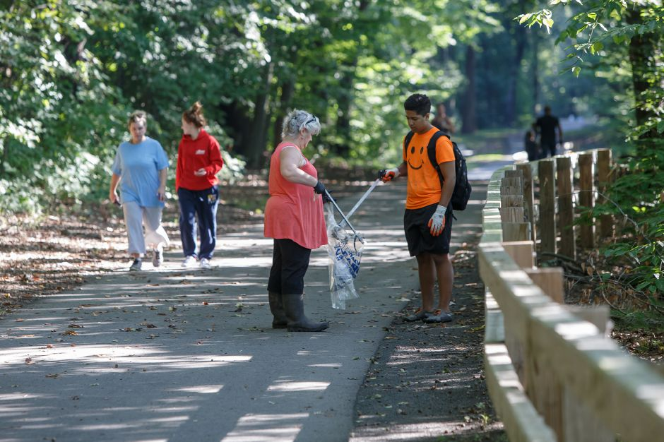 Lisa Burton left and Marcus Smith 15 of North Haven gather trash along the linear trail Saturday during the QRWA