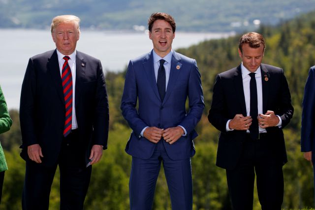 President Donald Trump, Canadian Prime Minister Justin Trudeau, and French President Emmanuel Macron participate in the family photo during the G-7 Summit, Friday, June 8, 2018, in Charlevoix, Canada. (AP Photo/Evan Vucci)
