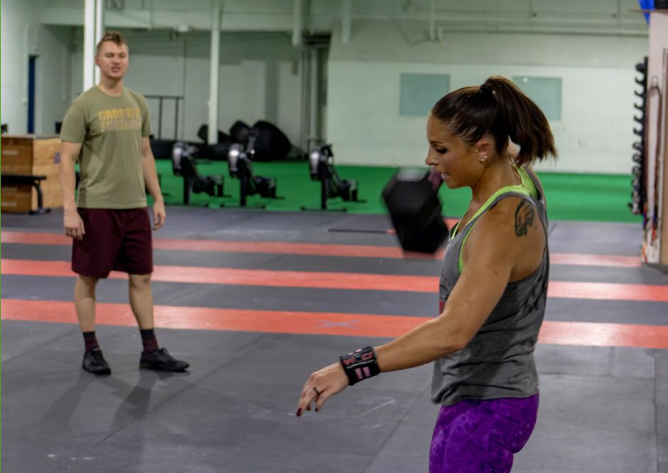 Coach Brandon Keegan, left, gives instructions as Jess Valentin works out at Meriden Crossfit Aug. 29, 2018. | Richie Rathsack, Record-Journal
