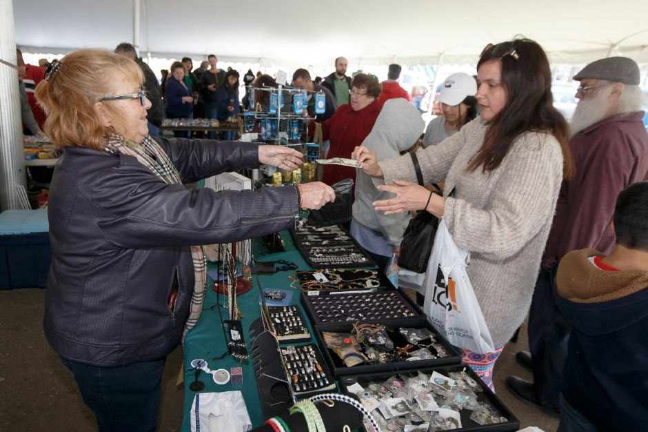 Jessica Paul of Middlebury makes a purchase from Connie Palazzo of Southington left in the tag sale tent Saturday during the Pre Daffodil Festival weekend at Hubbard Park in Meriden April 21, 2018 | Justin Weekes / Special to the Record-Journal
