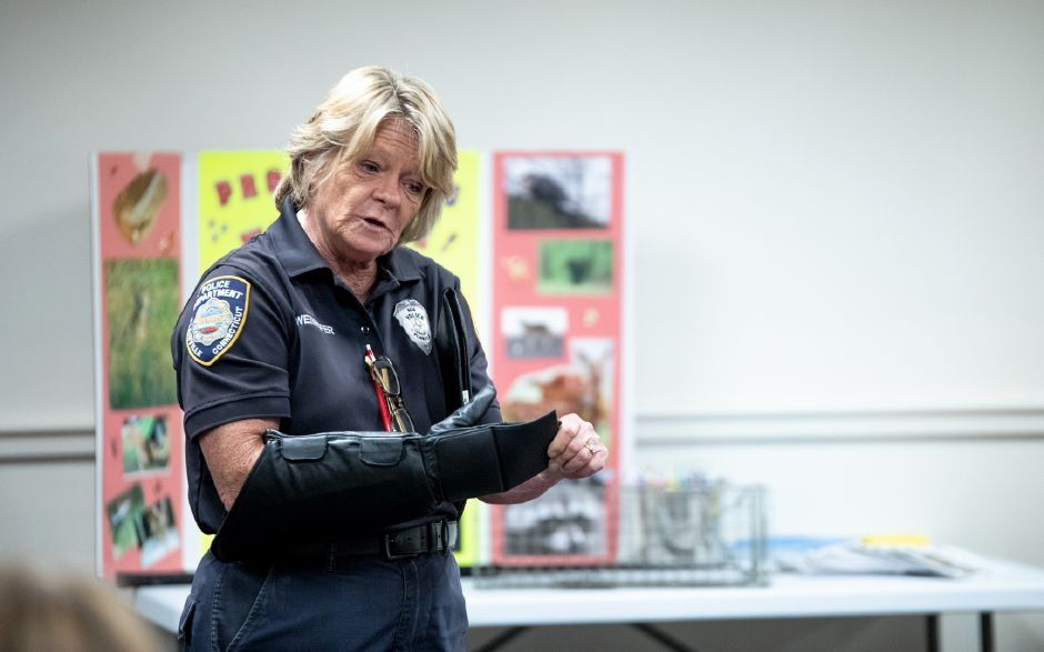 Plainville Animal Control Officer Donna Weinhofer shows a crowd of children the specialized gloves she uses when handling rabid animals. Weinhofer visited the Plainville Public Library Tuesday night to help families understand the animals which live around them. | Devin Leith-Yessian / Plainville Citizen