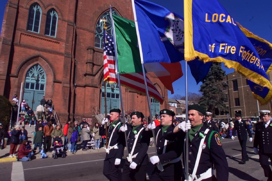 While the streets are lined with spectators, a colorguard of Meriden firefighters march down West Main Street in Meriden Saturday afternoon, during the St. Patricks Day parade.