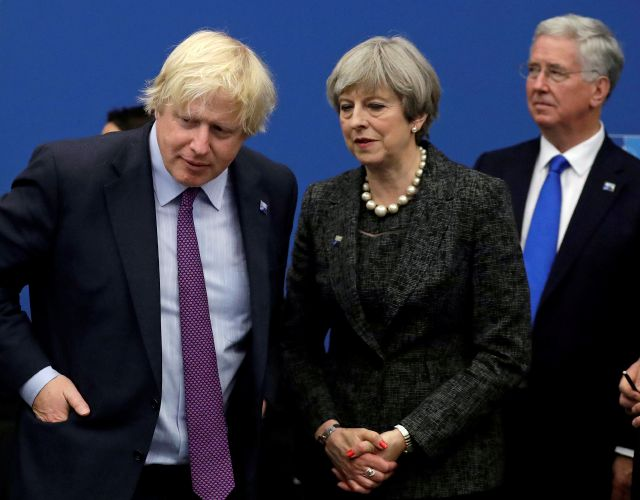 FILE - In this file photo dated Thursday, May 25, 2017, British Prime Minister Theresa May talks with British Foreign Minister Boris Johnson, with British lawmaker Michael Fallon, right, as they participate in a NATO summit of heads of state and government in Brussels. Prime Minister Theresa May has accepted the resignation of Boris Johnson Monday July 9, 2018, amid Cabinet splits over Brexit. (AP Photo/Matt Dunham, FILE)
