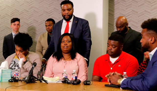 Amber Carr, left, wipes a tear as her sister Ashley Carr, center, talks about their sister, Atatiana Jefferson, as their brother, Adarius Carr, right and attorney Lee Merritt, standing, listen during a news conference Monday, Oct. 14, 2019 in downtown Dallas. The family of the 28-year-old black woman who was shot and killed by a white police officer in her Fort Worth home as she played video games with her 8-year-old nephew expressed outrage that the officer has not been arrested or...