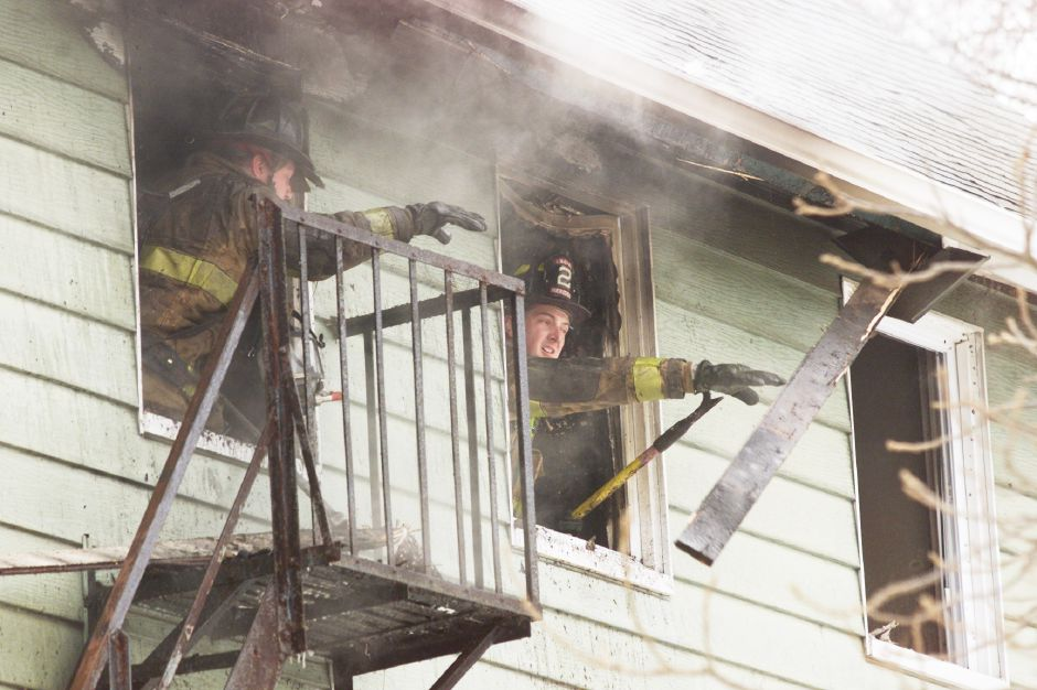 Meriden firefighters toss out chared debris from the third floor apartment of a house on Foster St. Fri. morning, Feb. 28 where a fire occured.