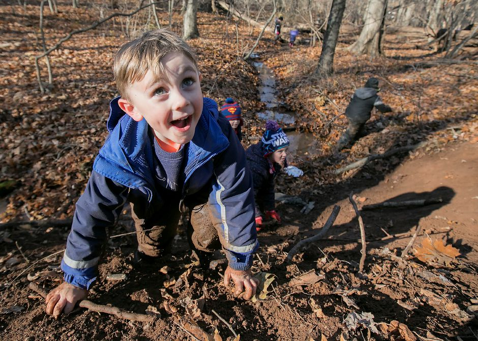 Moses Y. Beach Elementary School kindergarten student Austin Forant, 5, reaches the top of a muddy hill during the Kinderwoods program at Kohler Environmental Center in Wallingford, Thursday, Dec. 7, 2017. Dave Zajac, Record-Journal
