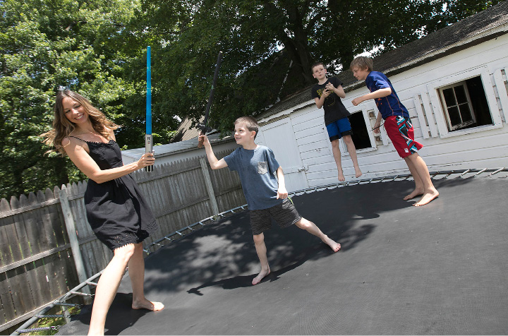 Left: Jessica Kastner, author of 'Hiding From The Kids In My Prayer Closet,' duels with son, Kenai, 7, on a trampoline at their home in Southington on Wednesday.    | Photos by Dave Zajac, Record-Journal