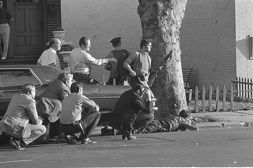 New York City police surround a small Brooklyn branch bank, Aug. 22, 1972, ready with arms behind a tree as two gunmen who described themselves as homosexuals, hold eight hostages inside the bank. The incident which began as a bank robbery was quickly cut off as some 200 policemen swarmed the scene. (AP Photo/Dave Pickoff)