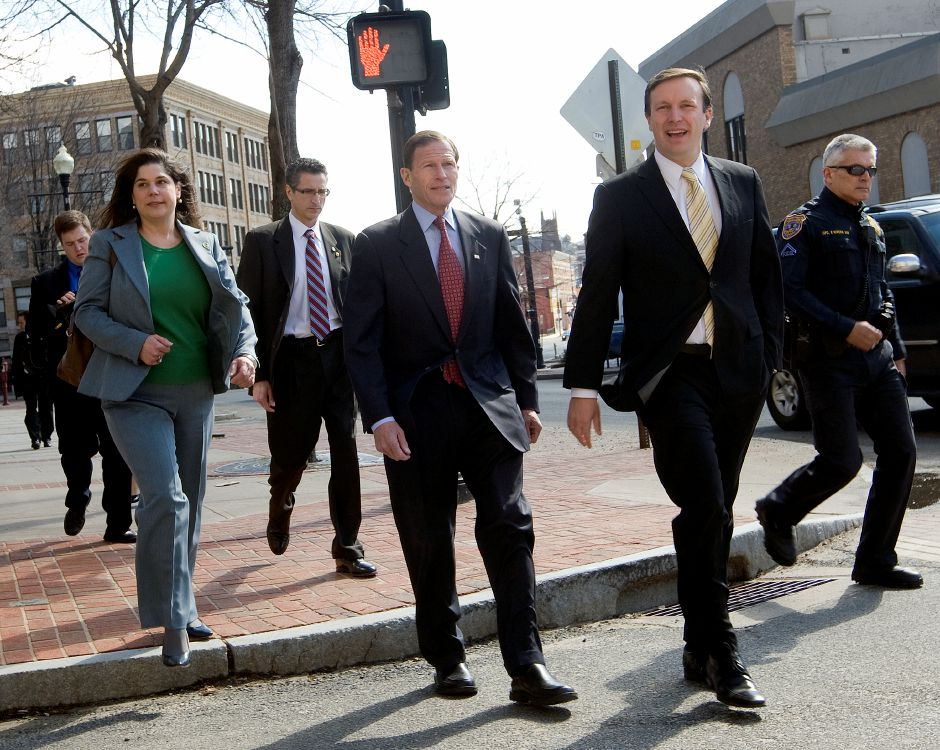 U.S. Senators Richard Blumenthal (D-Conn.), center, and Chris Murphy (D-Conn.), right, tour downtown businesses with State Sen. Dante Bartolomeo, D-Meriden, left, and Mayor Manny Santos after announcing the award of a $2.46 million federal grant to alleviate longtime major flooding in downtown Meriden. Officer Fred Rivera, far right, assists the group. | Dave Zajac / Record-Journal