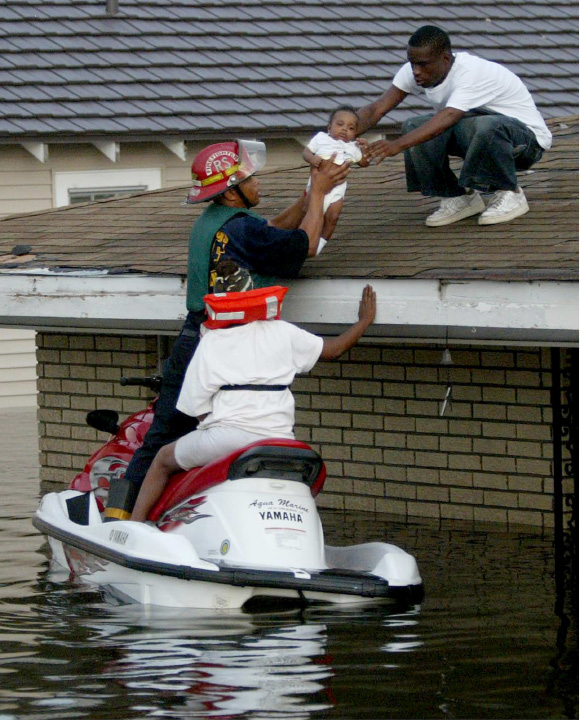 FILE - In this Monday, Aug. 29, 2005 file photo, Marshall Martin, on roof, hands 3-month-old Christopher Collins to New Orleans Fire and Rescue officer Jonathan Pajeaud while the child