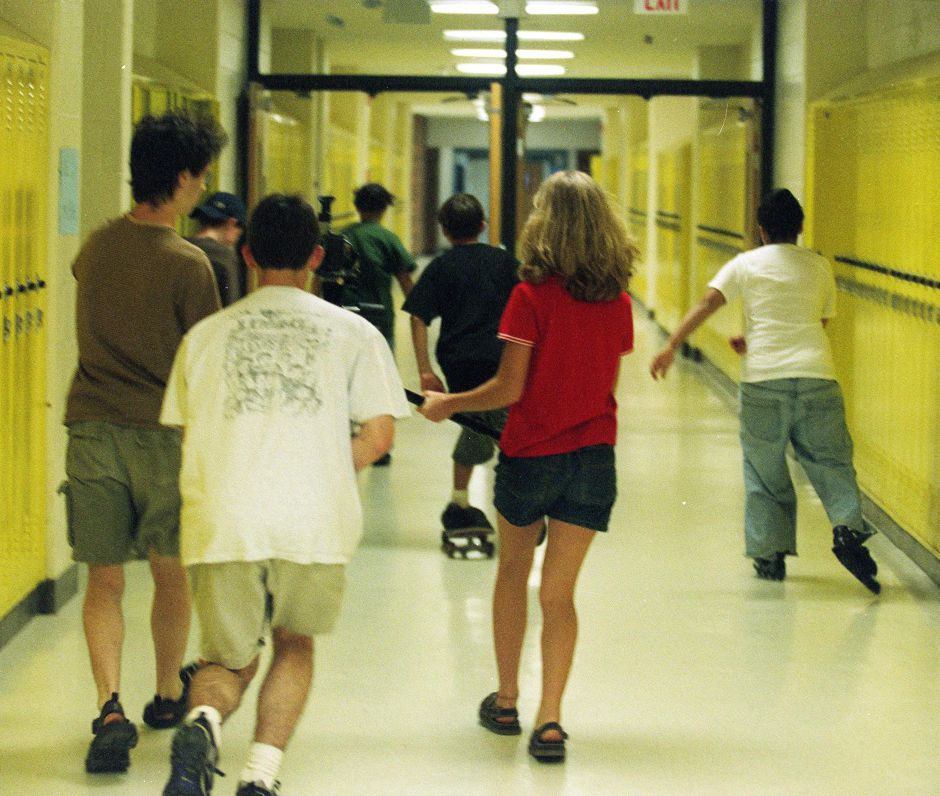 A team of young filmmakers chase volunteer actors on roller blades and skate boards down a hallway of Southington High School, Aug. 1999.