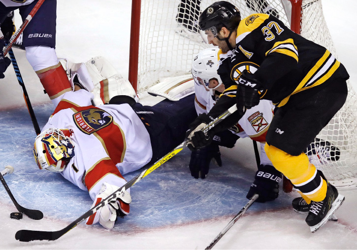 Florida Panthers goalie Roberto Luongo (1) drops to his back for a save as Boston Bruins center Patrice Bergeron (37) tries to get control of the puck the during the first period of an NHL hockey game in Boston, Monday, Dec. 5, 2016. (AP Photo/Charles Krupa)