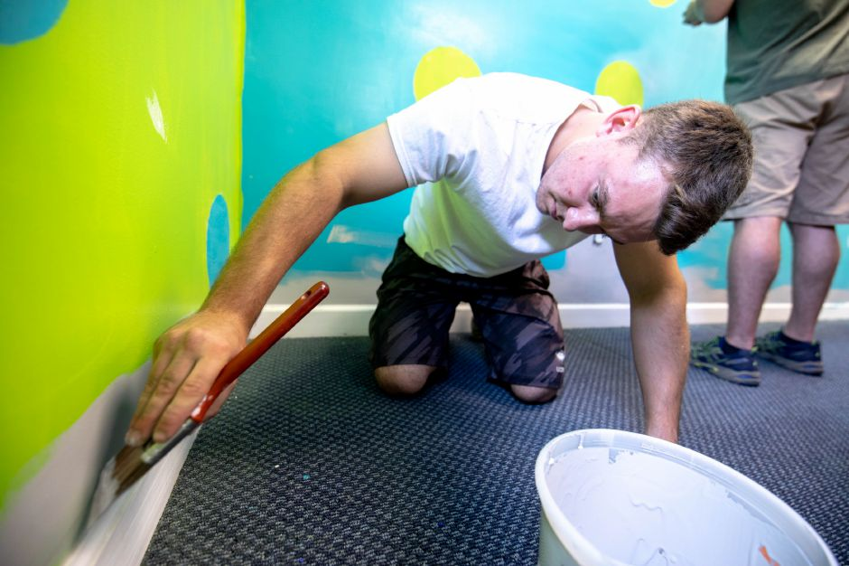 Josh Panczak, salesperson for Behr, repaints the walls of one of the buildings at Lisa Inc.