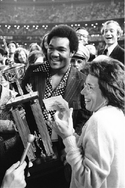 Heavyweight Champion George Foreman presents the winner's trophy and a check for $100,000 to Billie Jean King after she defeated Bobby Riggs in the winner-take-all tennis match at the Astrodome in Houston, Texas on Thursday, Sept. 21, 1973. Ms. King downed Riggs, 6-4; 6-3; 6-3. (AP Photo)