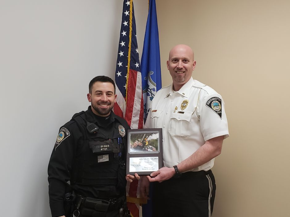 Officer Justin Burke, left, and Lt. Stephen Elliott, right, hold the award the Southington Police Department received for raising $2,500 for the Special Olympics Torch Run last year.