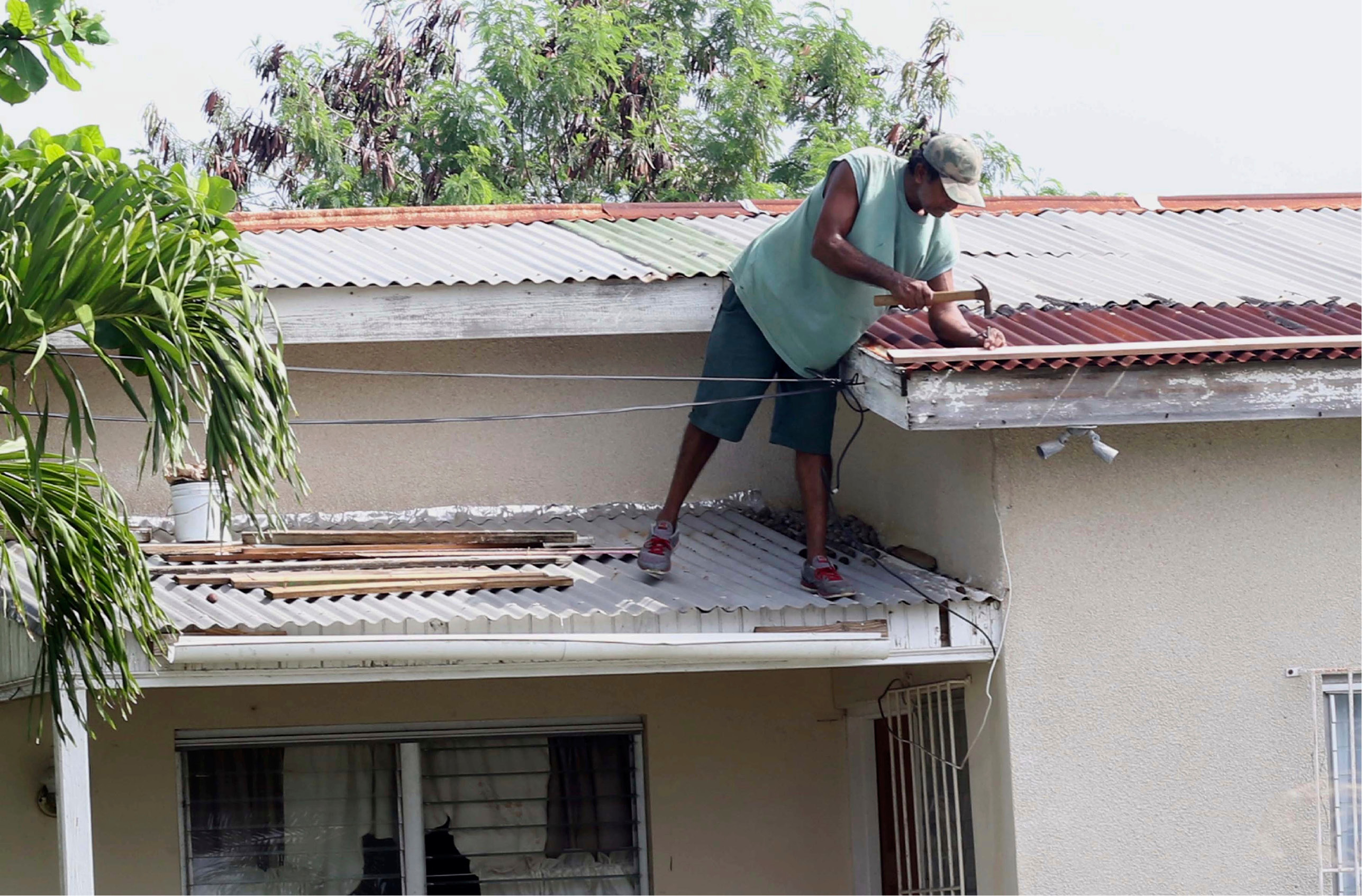 A homeowner makes last minute repairs to his roof in preparation for Hurricane Irma, in St. John