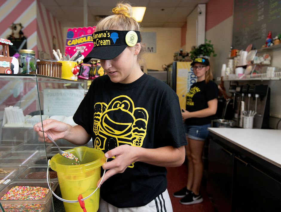 McKenzie Herget, manager, adds rainbow sprinkles to a Gone Bananas bucket sundae featuring six scoops of ice cream, sliced banana, four toppings, whipped cream and a cookie on Wednesday at Banana's Ice Cream in Wallingford.