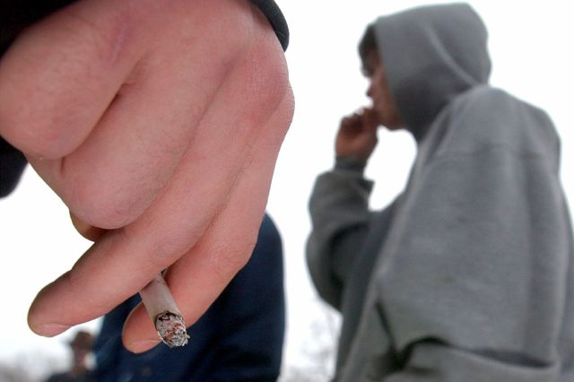 FILE - In this Tuesday, Dec. 10, 2002 file photo, a high school junior holds a cigarette as another high school student takes a drag in Lawrence, Kan. (Thad Allender/The Lawrence Journal-World via AP)