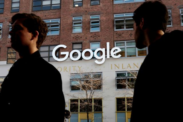 FILE - In this Dec. 4, 2017, file photo, people walk by Google offices in New York. Google is spending more than 1 billion to expand operations in New York City. Ruth Porat, senior vice president and chief financial officer at Google and Alphabet, said in a blog post Monday, Dec. 17, 2018, that Google is creating a more than 1.7 million square-foot campus that includes lease agreements along the Hudson River in lower Manhattan. (AP Photo/Mark Lennihan, File)