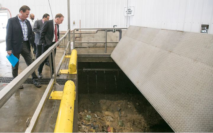 Southington town officials look over food waste in a mixer while touring Quantum Biopower in Southington, Wednesday, April 12, 2017. The recycling plant converts common food waste into combustible gas and energy. | Dave Zajac, Record-Journal
